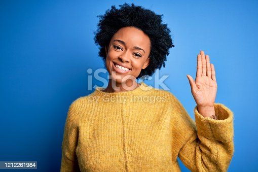 Young beautiful African American afro woman with curly hair wearing yellow casual sweater Waiving saying hello happy and smiling, friendly welcome gesture