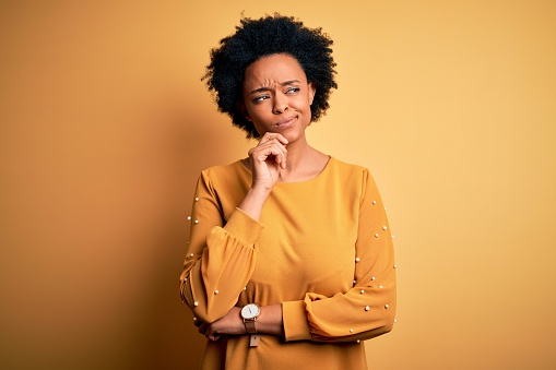 Young beautiful African American afro woman with curly hair wearing casual t-shirt with hand on chin thinking about question, pensive expression. Smiling with thoughtful face. Doubt concept.