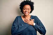 istock Young beautiful African American afro woman with curly hair wearing casual sweater smiling with hands on chest with closed eyes and grateful gesture on face. Health concept. 1212265526
