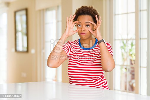 istock Young beautiful african american woman at home Trying to open eyes with fingers, sleepy and tired for morning fatigue 1143484662