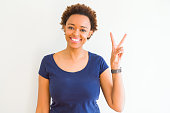 Young beautiful african american woman over white background showing and pointing up with fingers number two while smiling confident and happy.