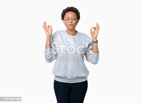 Young beautiful african american woman wearing glasses over isolated background relax and smiling with eyes closed doing meditation gesture with fingers. Yoga concept.