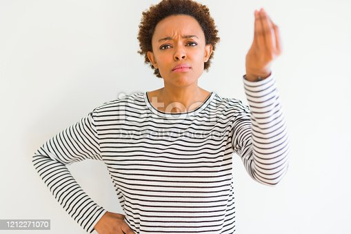 istock Young beautiful african american woman wearing stripes sweater over white background Doing Italian gesture with hand and fingers confident expression 1212271070