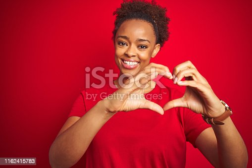 Young beautiful african american woman with afro hair over isolated red background smiling in love doing heart symbol shape with hands. Romantic concept.
