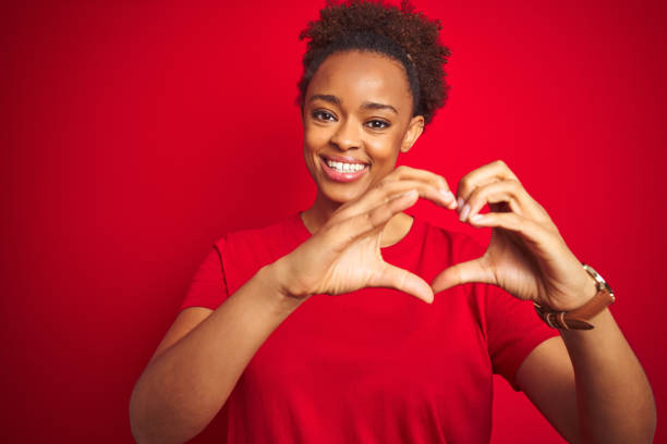 Young beautiful african american woman with afro hair over isolated red background smiling in love doing heart symbol shape with hands. Romantic concept. Young beautiful african american woman with afro hair over isolated red background smiling in love doing heart symbol shape with hands. Romantic concept. healthy heart stock pictures, royalty-free photos & images