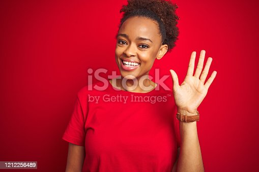 Young beautiful african american woman with afro hair over isolated red background Waiving saying hello happy and smiling, friendly welcome gesture
