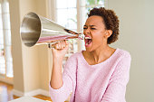 istock Young beautiful african american woman with afro hair screaming using megaphone 1212268557