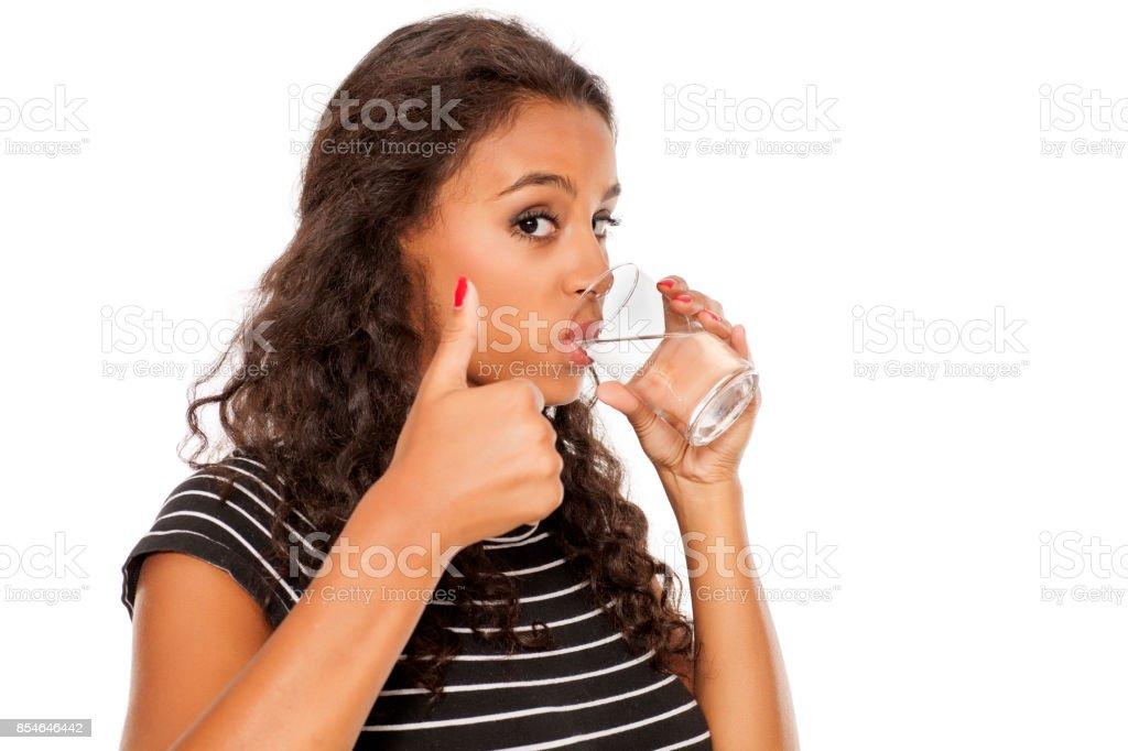 jeune fille africaine beau boire l'eau dans un verre et affichage des pouces vers le haut sur fond blanc - Photo