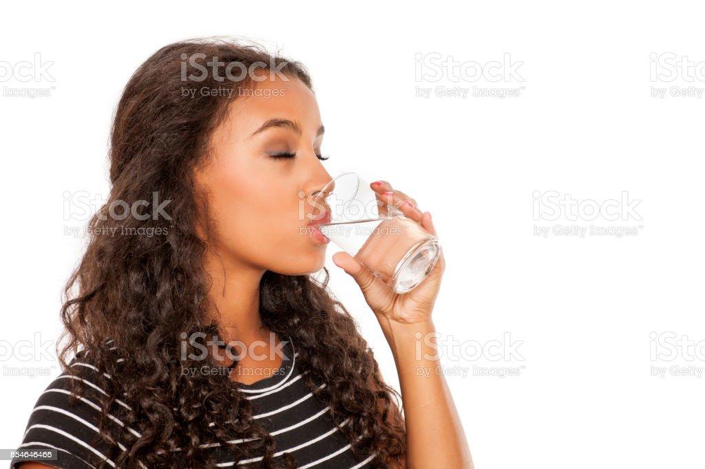 jeune fille africaine belle l'eau potable dans un verre sur fond blanc - Photo