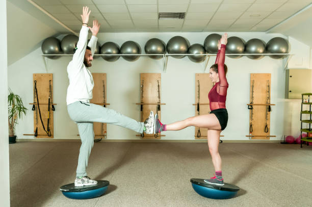 Young beautiful and attractive fitness couple workout on their balance by standing on the half ball on the one leg stock photo