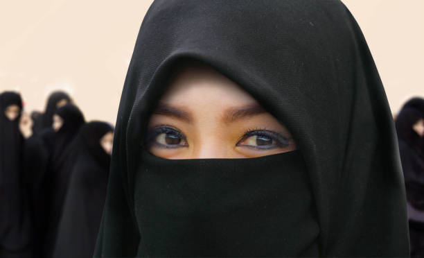 young beautiful and happy Muslim woman in traditional Islam burqa dress with amazing expressive eyes looking at the camera and group of women in black burka behind in religion and tradition concept stock photo