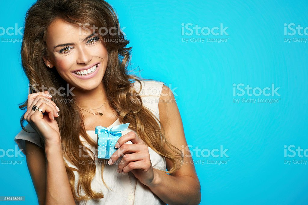 Young beautiful and happy woman with a gift Pretty girl with wrapped present on blue isolated background 2015 Stock Photo