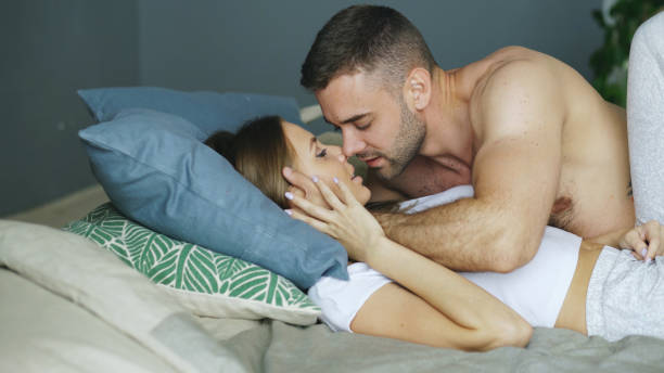 young beautiful and loving couple kissing on bed in the morning - naked women with animals stock photos and pictures