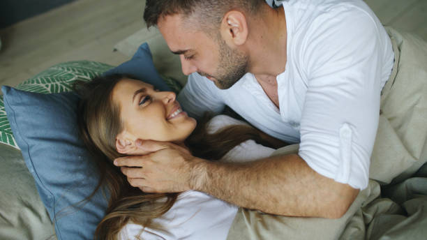 Young beautiful and loving couple wake up at the morning. Attractive man kiss and hug his wife in bed stock photo