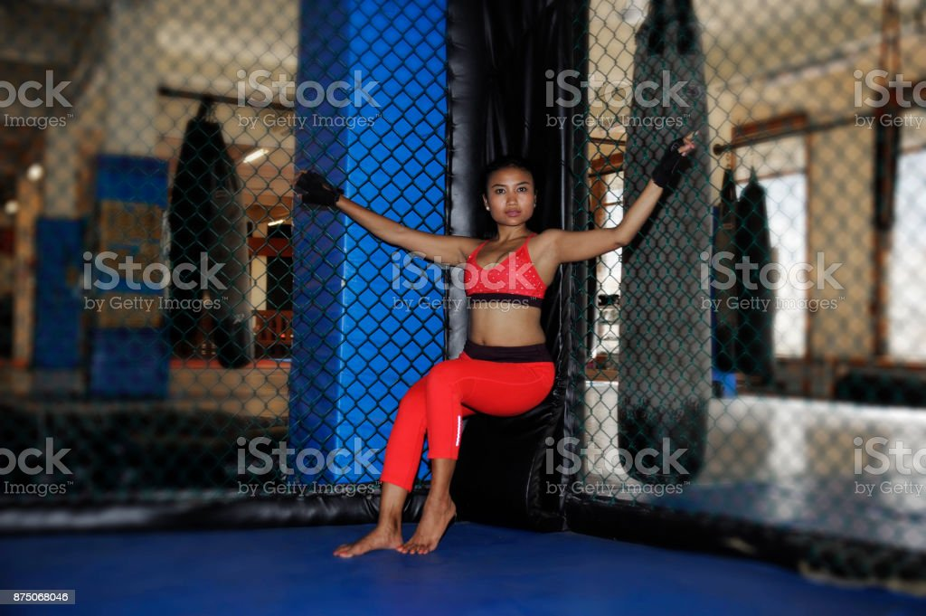 young beautiful and sexy Asian fighter woman in fighting gloves and...