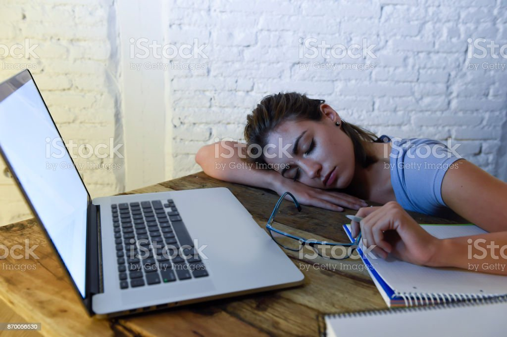 young beautiful and tired student girl sleeping taking a nap lying on home laptop computer desk exhausted and wasted spending night studying in stress preparing exam stock photo