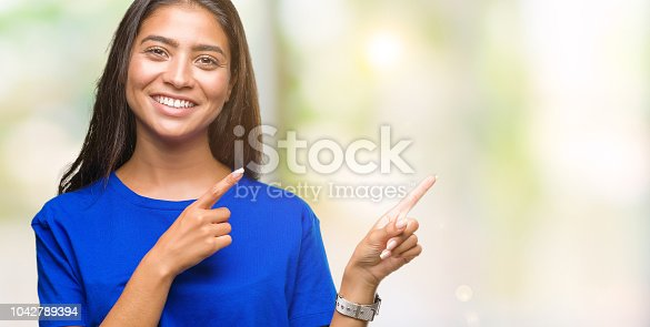istock Young beautiful arab woman over isolated background smiling and looking at the camera pointing with two hands and fingers to the side. 1042789394