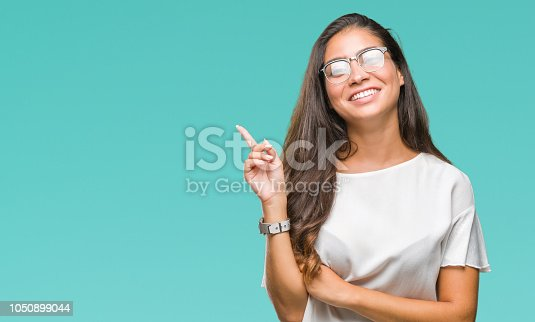 istock Young beautiful arab woman wearing glasses over isolated background with a big smile on face, pointing with hand and finger to the side looking at the camera. 1050899044