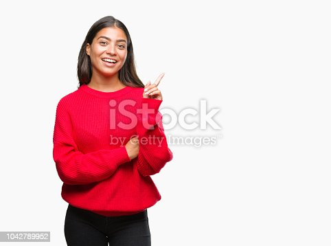 istock Young beautiful arab woman wearing winter sweater over isolated background with a big smile on face, pointing with hand and finger to the side looking at the camera. 1042789952