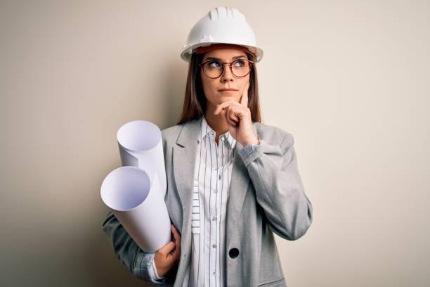 joven hermosa mujer arquitecta usando casco de seguridad y gafas sosteniendo planos serio cara pensando en la pregunta, idea muy confusa - arquitecta fotografías e imágenes de stock