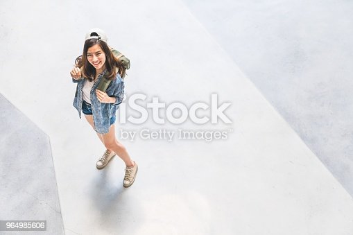 istock Young beautiful Asian backpack traveler girl looking up and smile, top view with copy space. Journey trip lifestyle, world travel explorer or tourism concept 964985606