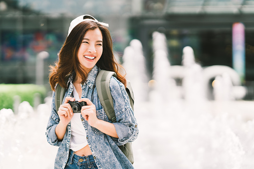 istock Young beautiful Asian backpack traveler woman using digital compact camera and smile, looking at copy space. Journey trip lifestyle, world travel explorer or Asia summer tourism concept 968545590