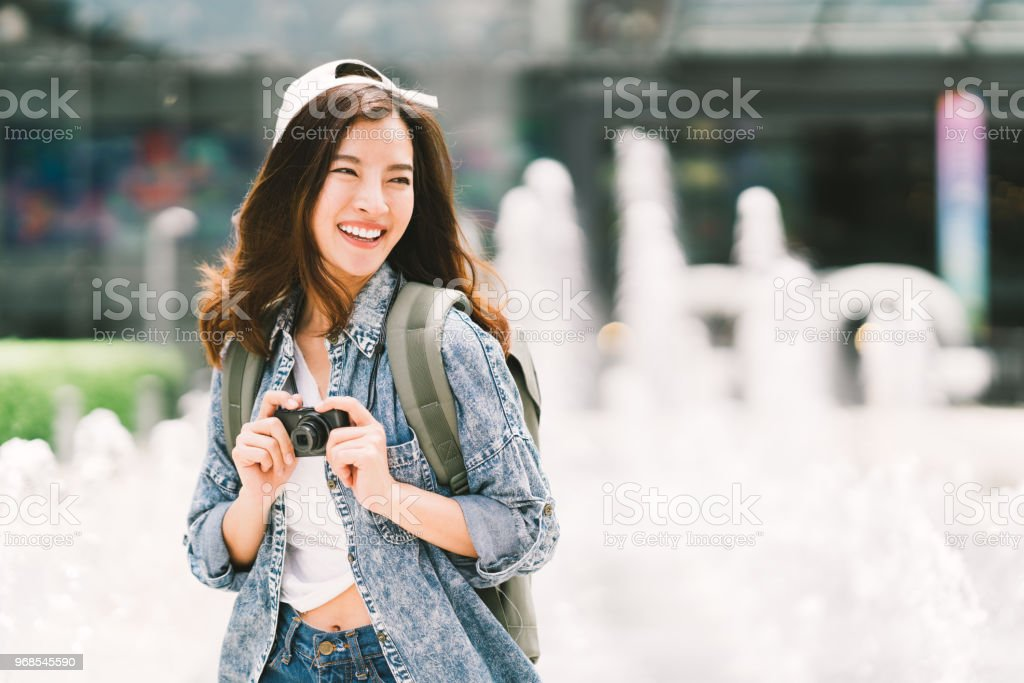 Young beautiful Asian backpack traveler woman using digital compact camera and smile, looking at copy space. Journey trip lifestyle, world travel explorer or Asia summer tourism concept stock photo