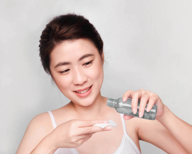 young beautiful asian girl with clean skin, Cosmetic Beauty Concept,hands touch on the cheek, smiling and friendly face isolated on grey background  A Beauty concept,Young beautiful asian woman with clean and bright skin, Holding a cotton swab to clean the face And skin toner toner bottle, Skin cleansing products skin care stock pictures, royalty-free photos & images