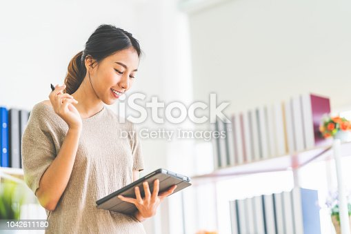 Young beautiful Asian girl working at home office using digital tablet, with copy space. Business owner entrepreneur, small business startup company, or casual freelance job lifestyle concept.