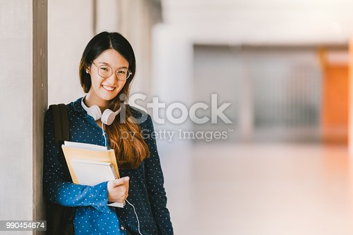 Young beautiful Asian high school girl or college student wearing eyeglasses, smiling in university campus with copy space. Education, geek or nerd people concept