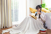 寝室の床に一人で座っているパジャマと眼鏡をかけた若い美しいアジアの10代の少女は、熱いコーヒーやお茶を飲みながら本を読んで楽しみます。ホームスクール学習でリラックスした女子�