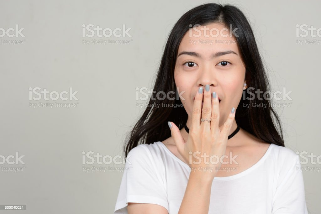 Young beautiful Asian woman against white background stock photo