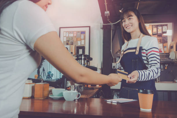 Young beautiful Asian woman barista wear blue apron and customer payment by credit card at bar counter in coffee shop with smile face.Concept of cafe and coffee shop small business. stock photo