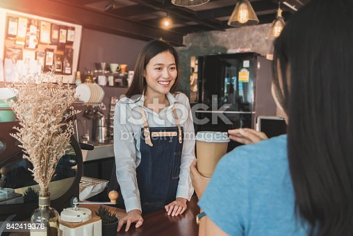 istock Young beautiful Asian woman barista wear blue apron talking to customer at bar counter in coffee shop with smile face.Concept of cafe and coffee shop small 842419376