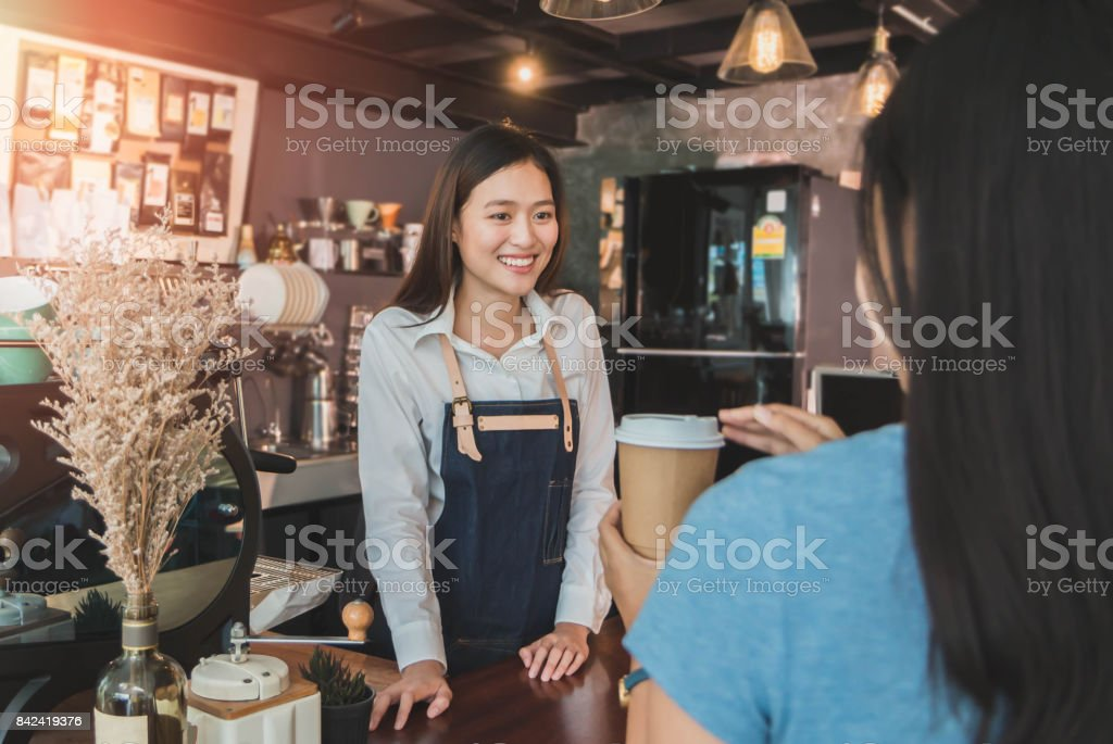 Young beautiful Asian woman barista wear blue apron talking to customer at bar counter in coffee shop with smile face.Concept of cafe and coffee shop small stock photo