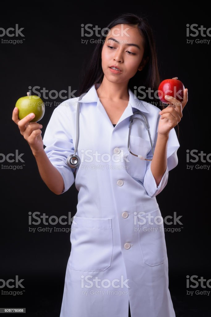 Young beautiful Asian woman doctor against black background stock photo