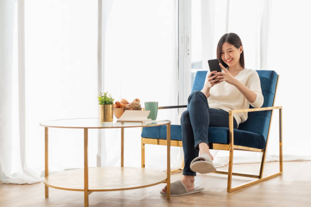 Young beautiful Asian woman relaxing in living room at home, reading books, drinking coffee and using phone in the morning with happy feeling stock photo
