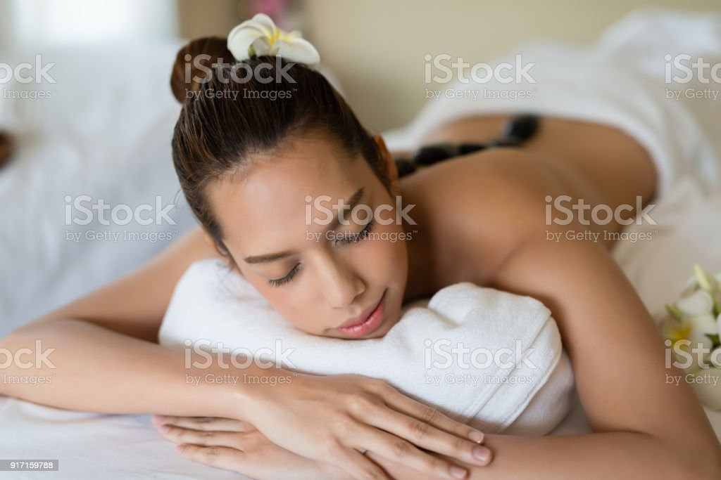 Young beautiful Asian woman relaxing in the Spa Stone Massage. Spa Hot  Stones - Stock image .