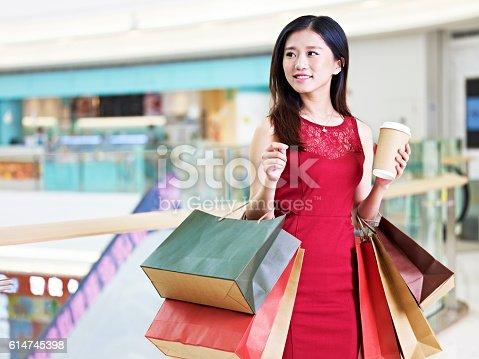istock young beautiful asian woman shopping in mall 614745398