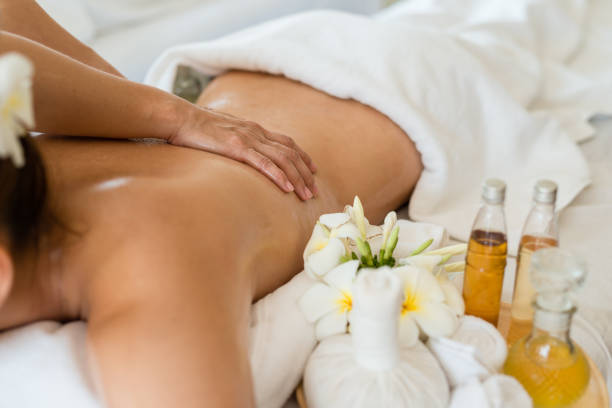 Young beautiful Asian woman sleep relaxing in the Oil spa massage in salon. Select focus hand of masseuse stock photo