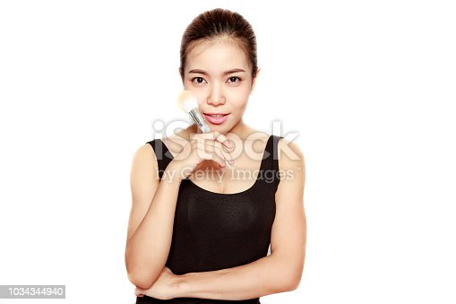 Sexy beautiful asian woman posing in studio with make-up brush on white background