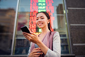 A young beautiful Asian woman using an application in her smart phone to check currency exchange rates in front of an illuminated information board. Communicate about money value, international