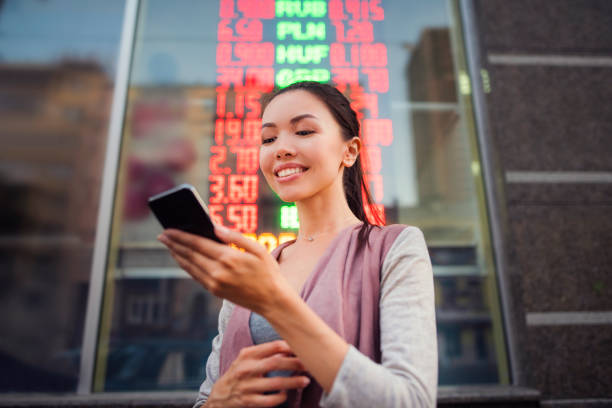 A young beautiful Asian woman using an application in her smart phone to check currency exchange rates in front of an illuminated information board. Communicate about money value, international A young beautiful Asian woman using an application in her smart phone to check currency exchange rates in front of an illuminated information board. Communicate about money value, international currency exchange stock pictures, royalty-free photos & images