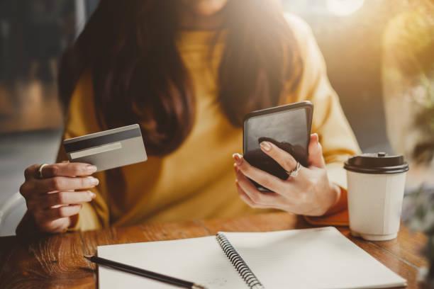junge schöne asiatin mit smartphone und kreditkarte für online-shopping in cafeteria café, vintage klangfarbe - konsum stock-fotos und bilder