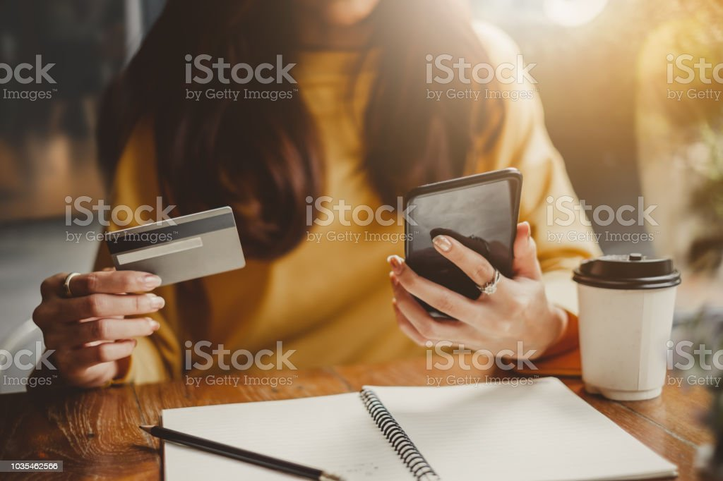 Young beautiful asian woman using smart phone and credit card for shopping online in coffee shop cafe, vintage tone color stock photo