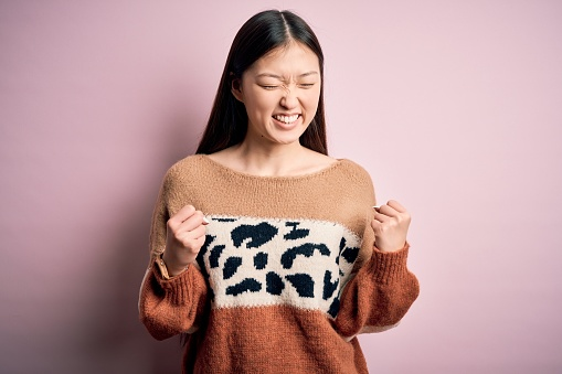 istock Young beautiful asian woman wearing animal print fashion sweater over pink isolated background excited for success with arms raised and eyes closed celebrating victory smiling. Winner concept. 1213719996