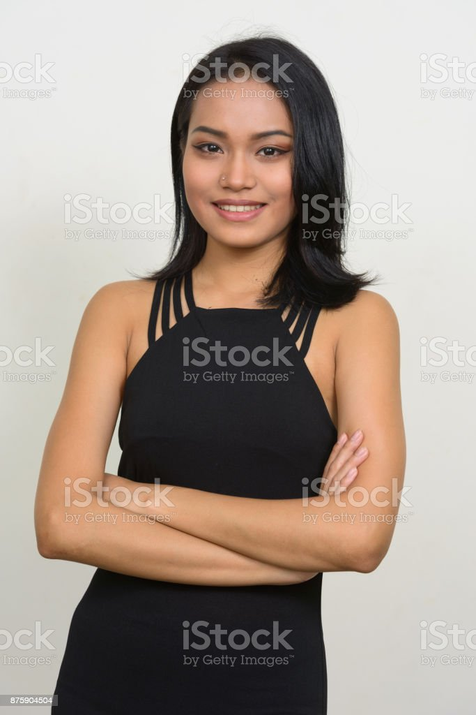 d0dad4735e4 Young beautiful Asian woman wearing black sleeveless dress against white  background royalty-free stock photo