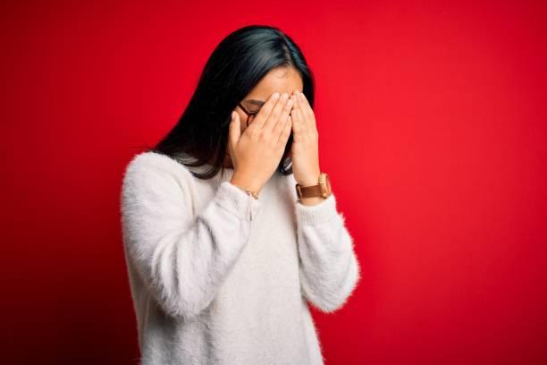 joven hermosa mujer asiática con suéter casual y gafas sobre fondo rojo con expresión triste cubriendo la cara con las manos mientras llora. concepto de depresión. - vergüenza fotografías e imágenes de stock