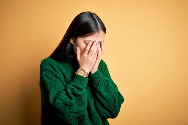 joven hermosa mujer asiática con suéter de invierno verde sobre fondo aislado amarillo con expresión triste que cubre la cara con las manos mientras llora. concepto de depresión. - vergüenza fotografías e imágenes de stock
