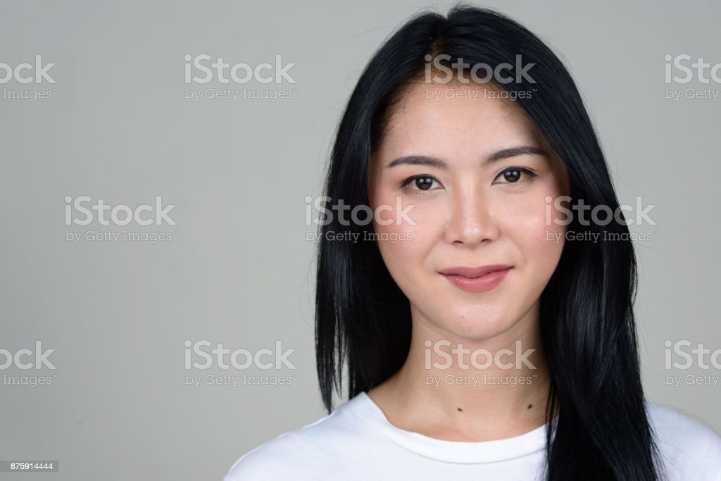 Young beautiful Asian woman wearing white shirt against white background stock photo